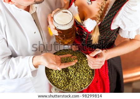 Woman in Tracht and brewer with beer stein and hops in her brewery