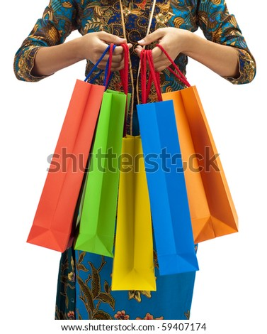 Woman in tradition Kebaya holding colorful shopping bag.