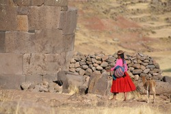 Woman in traditional clothes with lama sitting on stone in Puno - Peru.