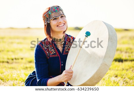 woman in traditional ethnic clothes playing drum