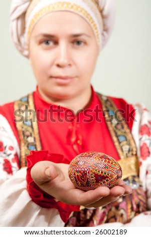 Woman in traditional Russian dress and hat is holding an easter egg.