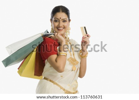 Woman in traditional South Indian sari holding shopping bags with a credit card and smiling