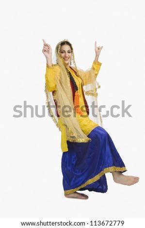 Woman in traditional yellow Punjabi dress doing bhangra - stock photo