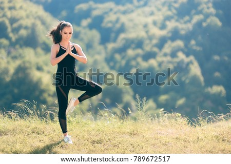 Woman in Tree Yoga Pose Wearing  Overall Jumpsuit Exercising Outside. Fit girl in sporty outfit active wear outdoors in nature ready to exercise  #789672517