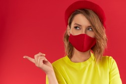 Woman in trendy fashion outfit during quarantine of coronavirus outbreak. Model dressed protective stylish handmade face mask on red studio background