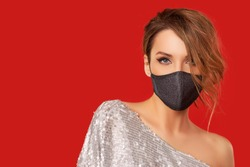Woman in trendy fashionable outfit during quarantine of coronavirus outbreak. Model dressed stylish protective face mask on red studio background