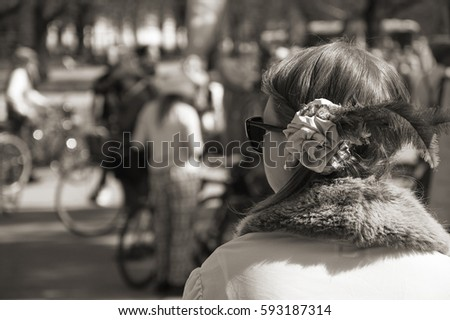 Woman in tweed ride costume with fur collar, feather in hairstyle and sunglasses looking at the street full of event participants with bicycles. Large group of people on sunny spring day. Sepia tones.