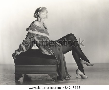 Woman in velvet dress sitting on footstool