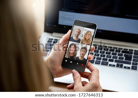 Woman in video conference with a group of people. Young business woman having a video chat with coworkers on her mobile phone. Woman in her workplace with smartphone in her hands.
