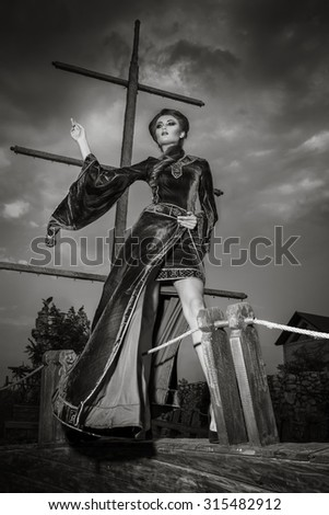 Woman in vintage fashion old clothes on boat peak cap. Fashion old vintage style concept. Rich attractive woman on boat. Black and white image