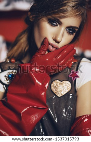 Woman in vinyl clothes. Portrait of woman in vinyl red gloves and detailed top