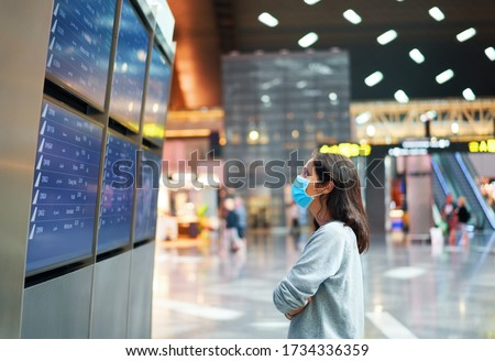 Photo of  Woman in virus protection face mask looking at information board checking her flight in international airport. Departure board, flight status