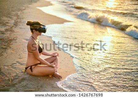 Woman in VR glasses doing yoga padmasana on ocean beach in the morning. Girl using virtual reality for deep immersion to feel herself at the seaside concept. Yoga online internet lessons with coach. #1426767698