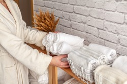 Woman in warm bathrobe is placing basket of rolled cotton bath towels on wooden shelf of linen closet together with bed sheets, blankets, duvet and vase against white brick wall. Marie Kondo method.