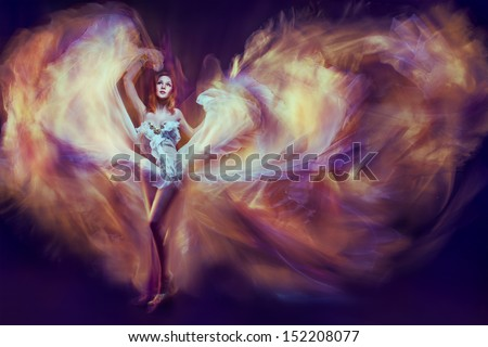 Stock Photo Woman in waving dress as a flame dancing with flying fabric. Dark background