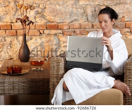 Woman in wellness environment sitting in armchair using laptop computer.?