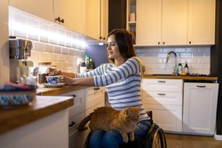 Woman in wheelchair in kitchen at home