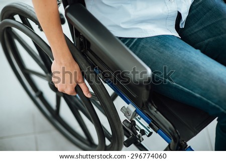 Woman in wheelchair\'s hand on wheel close up, disability and handicap concept