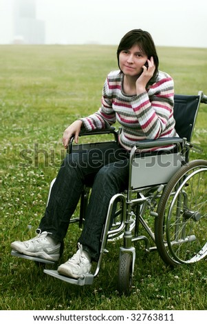 Woman in wheelchair talking by phone in park