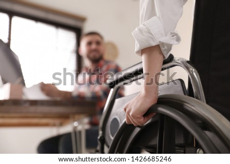 Woman in wheelchair with her colleague at workplace, closeup #1426685246