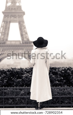 Woman in white coat and black hat in Paris in front of the Eiffel tower. Black and white picture