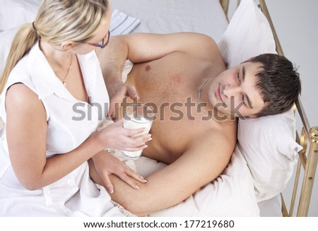 Woman in white coat caring sick man with a milk