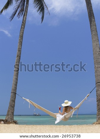 woman in white dress and hat on the beach with cocktail
