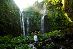 Woman in white dress at the Sekumpul waterfalls in jungles on Bali island, Indonesia
