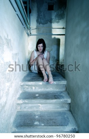 woman in white dress crouches on the basement stairs