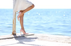 woman in white dress leaning standing by the sea side looking at the sea with stilettos