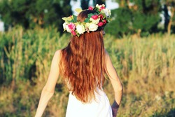 Woman in white dress standing in field wearing flower crown. Young forest inspired bride, bohemian girl