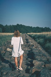 Woman in white dress walking along the stone pier at sunny hot day. High quality photo