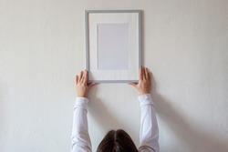 Woman in white hoody hanging vertical empty frame on white wall to create family photo gallery, to capture a moment, mockup template on white background, lifestyle