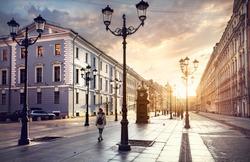 Woman in white jacket walking Malaya Konyushennaya  street with Lanterns and ol buildings in Saint Petersburg