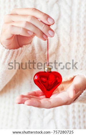 Woman in white knitted sweater holding Christmas decoration - bright red heart. Sparkling, shiny symbol of love. Holiday New Year or Valentine's Day background. #757280725