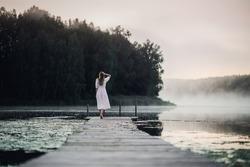 Woman in white light dress run on the pier on foggy morning lake.