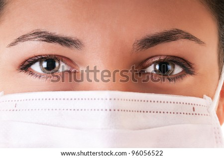 Woman in white medical mask. Selective focus on eyes.