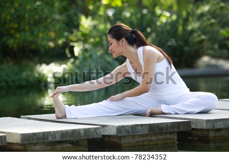 Woman in white Performing yoga in natural setting - stock photo