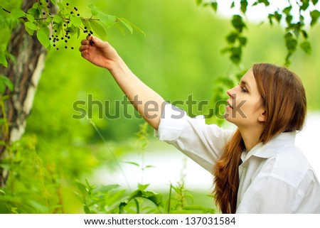 Woman in white picking chokecherries