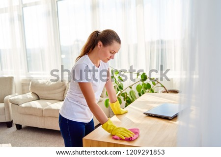 Woman in white shirt and yellow protective rubber gloves cleaning at home and wiping dust on wooden tablel with pink rag, copy space. Housework, cleanig and chores concept #1209291853