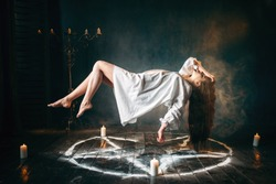 Woman in white shirt flying over pentagram circle