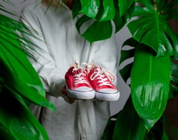 Woman in white shirt show red gumshoes near palm leaves.