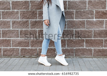Woman in white sneakers and blue jeans, gray coat near a brick wall
