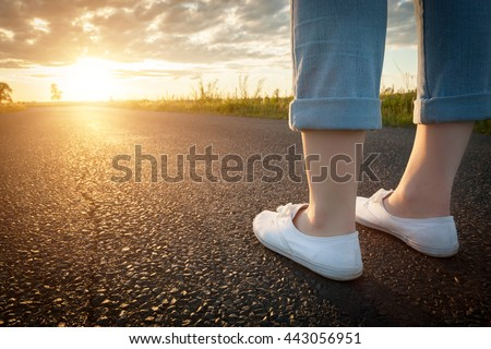 Woman in white sneakers standing on asphalt road towards sun. Concept of new start, travel, freedom etc.