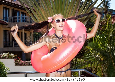 Woman in white sunglasses with pink inner tube pulls her hair in different directions for the two arms of the tail . Outdoors