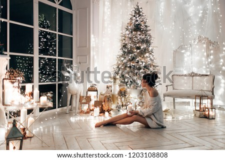 woman in white sweater, warm and cozy evening in Christmas interior design, Xmas tree decorated by lights gifts toys, candles, lanterns, garland lighting indoors fireplace.holiday living room.New year
