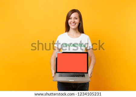 Woman in white t-shirt written inscription green title volunteer hold laptop pc computer, blank empty screen isolated on yellow background. Voluntary free assistance help, charity grace work concept