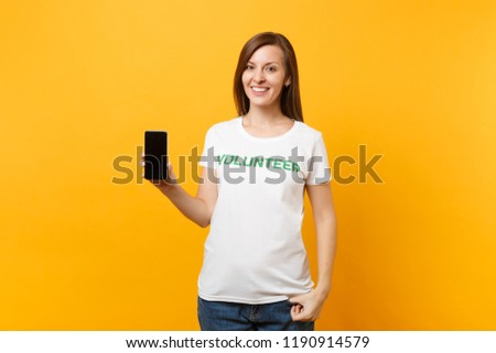 Woman in white t-shirt written inscription green title volunteer hold mobile phone with blank empty screen isolated on yellow background. Voluntary free assistance help, charity grace work concept