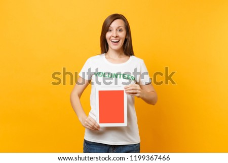 Woman in white t-shirt written inscription green title volunteer hold tablet pc computer, blank empty screen isolated on yellow background. Voluntary free assistance help, charity grace work concept