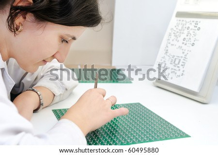 Woman in white uniform checking or assembling components and chip on integrated microcircuit